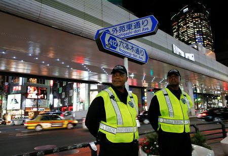 Japanese security firm Executive Protection Inc. employees, 49-year-old Eddie Lee Davis of the U.S. and his compatriot, 59-year-old Antonio Nathaniel King, stand guard on the street at Roppongi shopping and amusement district in Tokyo, Japan November 1, 2018. Picture taken November 1, 2018.  REUTERS/Issei Kato