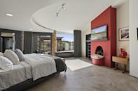<p>The muted red fireplace really grabs your attention.</p>