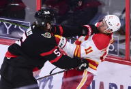 Ottawa Senators defenseman Mike Reilly (5) gives Calgary Flames center Mikael Backlund (11) a shove during second period NHL hockey action in Ottawa on Monday, March 1, 2021. (Sean Kilpatrick/The Canadian Press via AP)