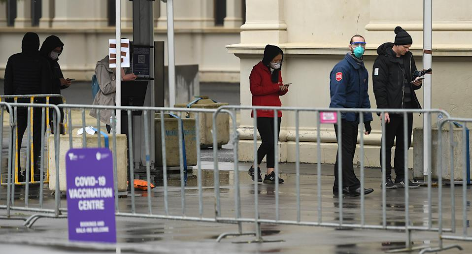 People are seen waiting in a line outside the vaccination centre at the Royal Exhibition Building in Melbourne. Source: AAP