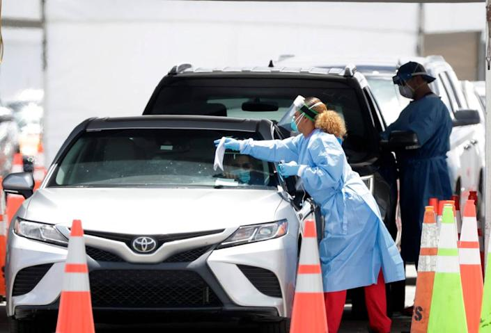 Healthcare workers prepare to test drivers at a drive-through coronavirus testing site outside of Hard Rock Stadium, Friday, June 26, 2020, in Miami Gardens, Fla.