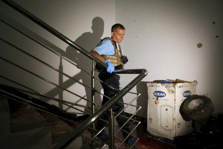 A U.N. official walks at a staircase covered in blood in the Radisson hotel in Bamako, Mali, November 20, 2015. REUTERS/Joe Penney