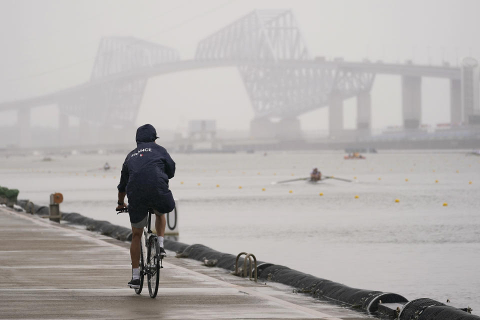 A coach from France rides her bike as rowers train during a rowing training session at the 2020 Summer Olympics, Tuesday, July 27, 2021, in Tokyo, Japan. (AP Photo/Darron Cummings)