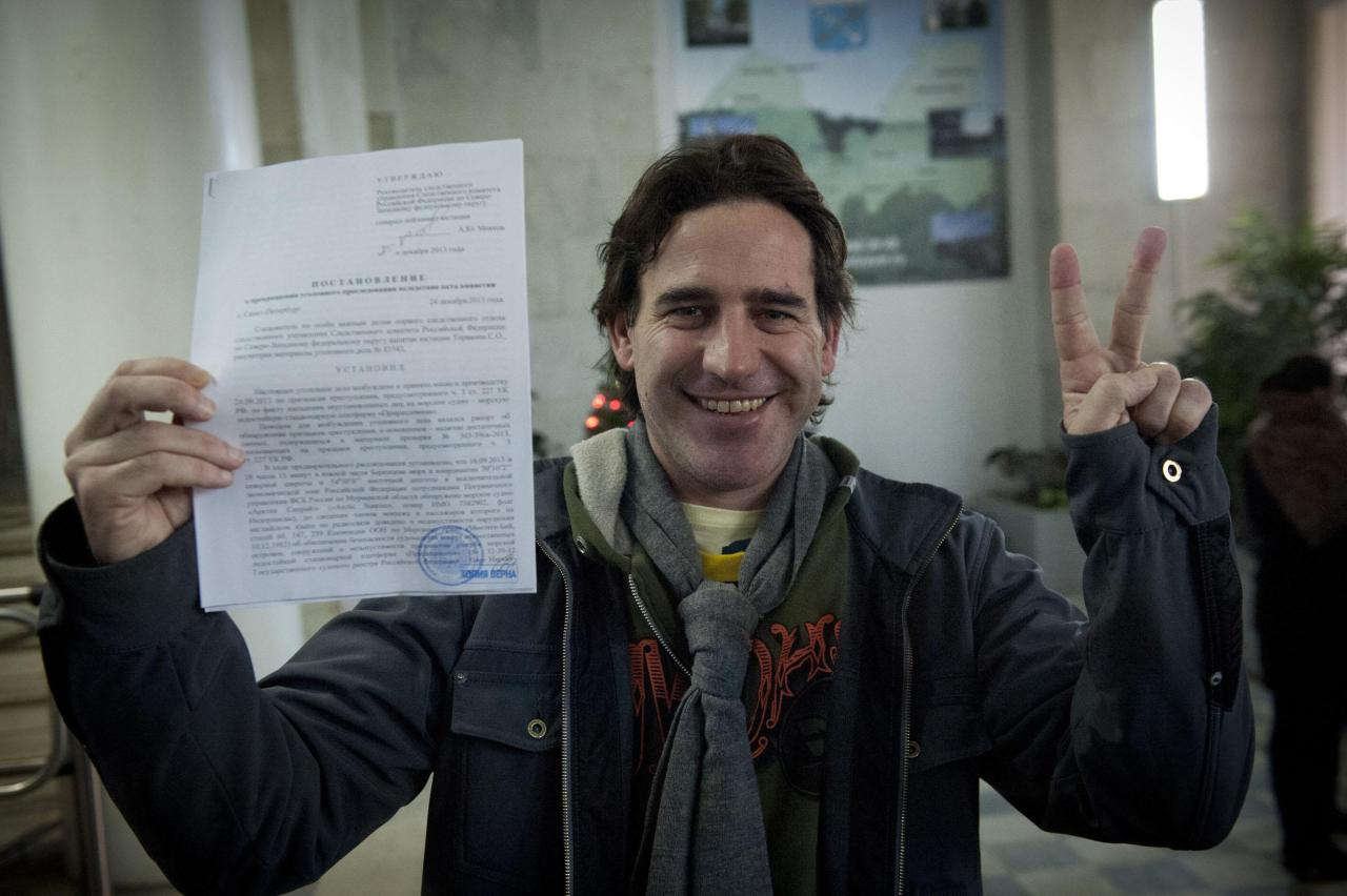 Greenpeace International activist Miguel Hernan Perez Orsi from Argentina holds up papers certifying the termination of his criminal prosecution, after having the criminal charges against him dropped, in Saint Petersburg, December 25, 2013, in this handout image courtesy of Greenpeace. Russia formally dropped criminal charges against the Greenpeace activists arrested in a protest over Arctic oil drilling on Wednesday, under a Kremlin amnesty extended to all 30 who had been facing up to seven years jail if convicted. REUTERS/Dmitri Sharomov/Greenpeace/Handout via Reuters (RUSSIA - Tags: CIVIL UNREST ENERGY CRIME LAW HEADSHOT) ATTENTION EDITORS � THIS IMAGE WAS PROVIDED BY A THIRD PARTY. NO SALES. NO ARCHIVES. FOR EDITORIAL USE ONLY. NOT FOR SALE FOR MARKETING OR ADVERTISING CAMPAIGNS. NO THIRD PARTY SALES. NOT FOR USE BY REUTERS THIRD PARTY DISTRIBUTORS. MANDATORY CREDIT. THIS PICTURE IS DISTRIBUTED EXACTLY AS RECEIVED BY REUTERS, AS A SERVICE TO CLIENTS