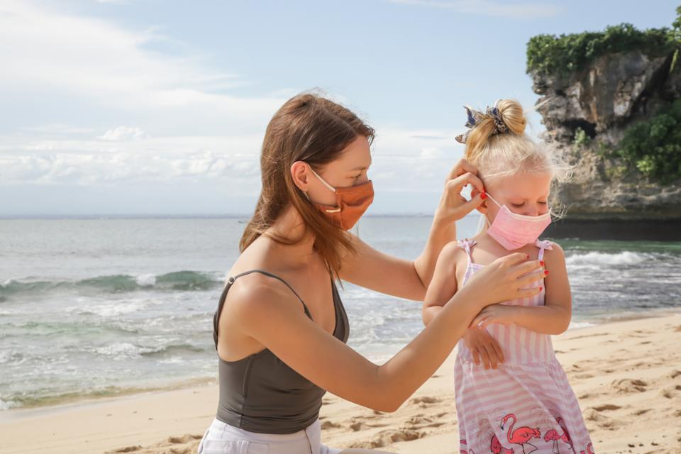 Summer vacation after Coronavirus pandemic crisis. Adorable toddler girl and her mum wearing protective masks on the sandy beach.