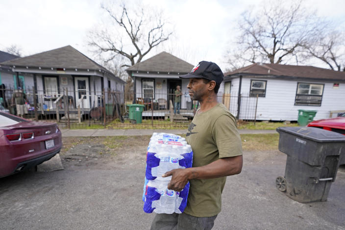 Ernest Collins carries cases of water back to his home, which was without running water for days after a recent winter storm, Friday, Feb. 26, 2021, in Houston. Local officials, including Houston Mayor Sylvester Turner, say they have focused their efforts during the different disasters on helping the underserved and under-resourced but that their work is far from complete. (AP Photo/David J. Phillip)