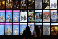 People look at the movies screen board at Mall of the Emirates during the reopening of malls, following the outbreak of the coronavirus disease (COVID-19), in Dubai