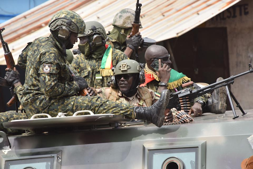 Pictured here, Members of Guinea's armed forces celebrate after the arrest of Guinea's president, Alpha Conde.