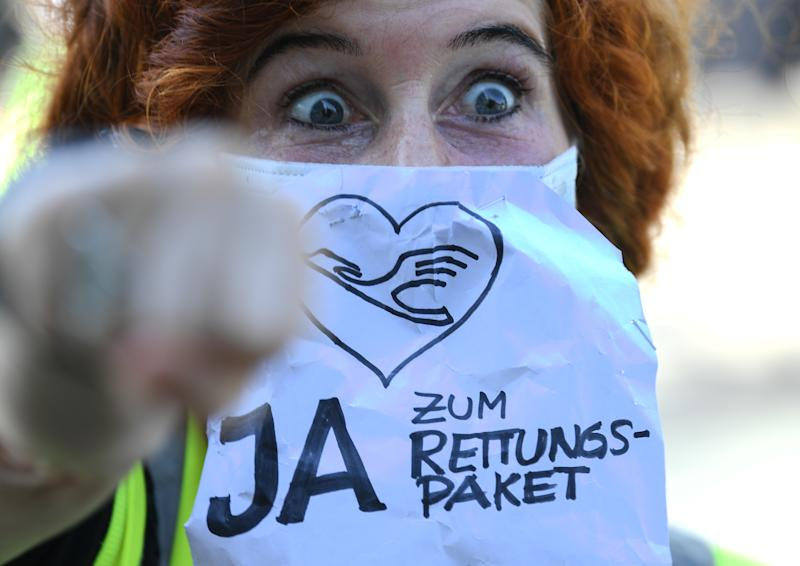 "25 June 2020, Hessen, Frankfurt/Main: During a demonstration in front of Lufthansa headquarters at Frankfurt Airport, a Lufthansa flight attendant wears a mouth guard with the words ""Yes to the rescue package"". The company's shareholders decide at the Extraordinary General Meeting whether or not they want the state to become a shareholder for about 300 million euros. Photo: Arne Dedert/dpa (Photo by Arne Dedert/picture alliance via Getty Images)"