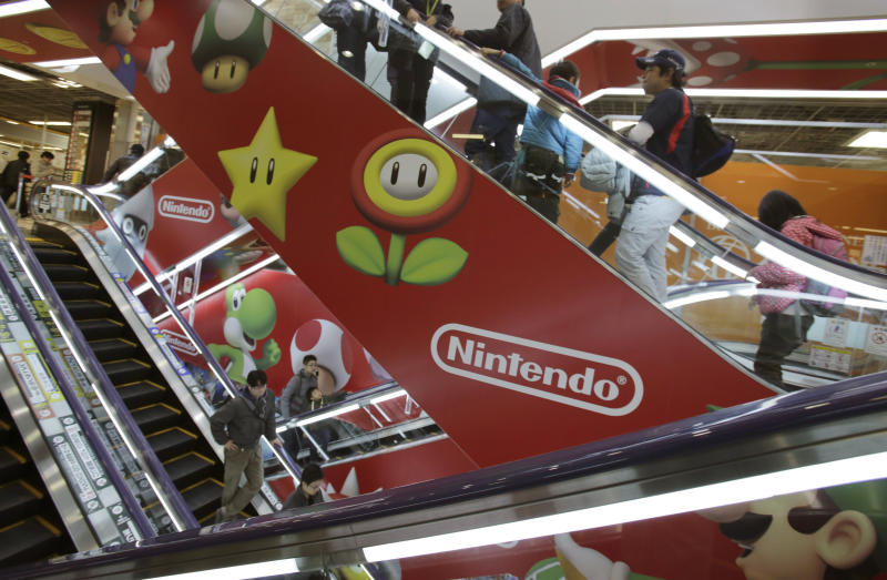 In this photo taken Sunday, Dec. 15, 2013, shoppers take escalators under the logo of Nintendo and Super Mario characters at an electronics store in Tokyo. This holiday season Nintendo faces a critical test with its Wii U video game console that is pitted against Sony's PlayStation 4 and Microsoft's Xbox One as it seeks to revive flagging sales. (AP Photo/Shizuo Kambayashi)
