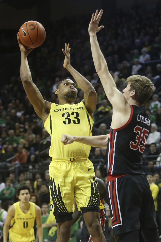 Oregon's Francis Okoro, left, shoots over Utah's Branden Carlson during the first half of an NCAA college basketball game in Eugene, Ore., Sunday, Feb. 16, 2020. (AP Photo/Chris Pietsch)
