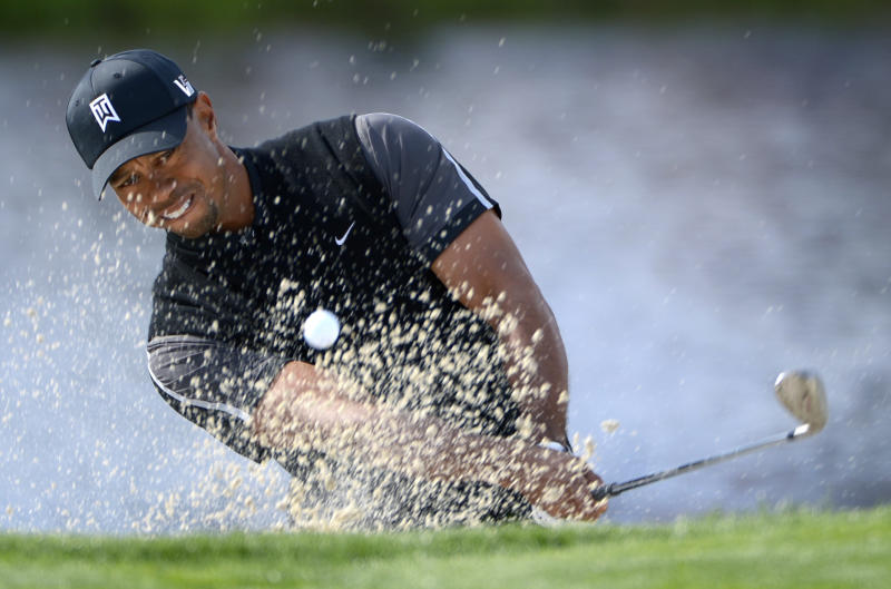 Tiger Woods hits out of a bunker onto the 17th green during the first round of the Arnold Palmer Invitational golf tournament in Orlando, Fla., Thursday, March 21, 2013.(AP Photo/Phelan M. Ebenhack)