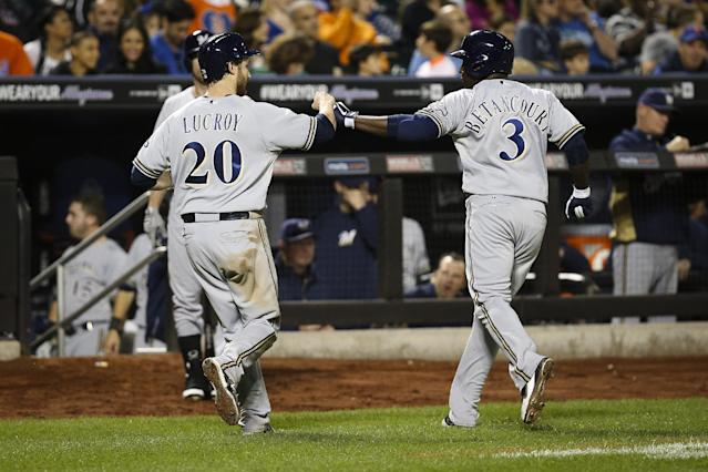 Milwaukee Brewers first baseman Yuniesky Betancourt (3) celebrates after his sacrifice fly to left field drove catcher Jonathan Lucroy (20) home in the eighth inning of a baseball game against the New York Mets at Citi Field, Saturday, Sept. 28, 2013, in New York. (AP Photo/John Minchillo)