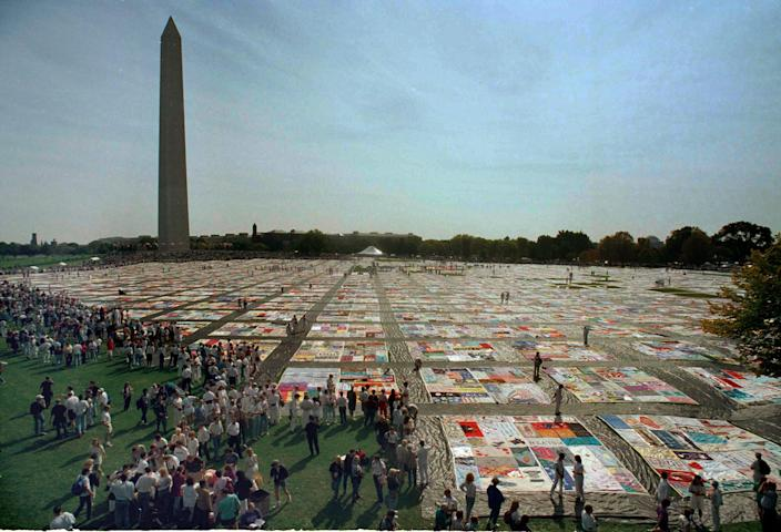 In this Saturday, Oct. 10, 1992 file picture, volunteers and others walk on the 21,000 panel Names Project AIDS Memorial Quilt in Washington.