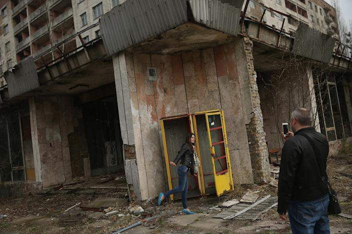 <p>Tourists on a guided tour snap photos of one another outside an abandoned shop and apartment building (Getty Images) </p>