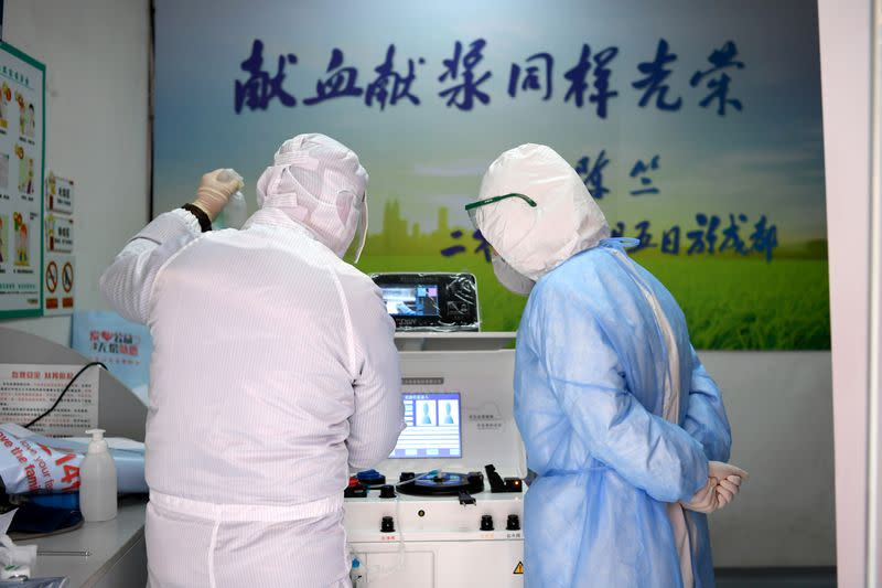 Medical workers in protective suits inspect equipment at a blood donation room of the Renmin Hospital of Wuhan University