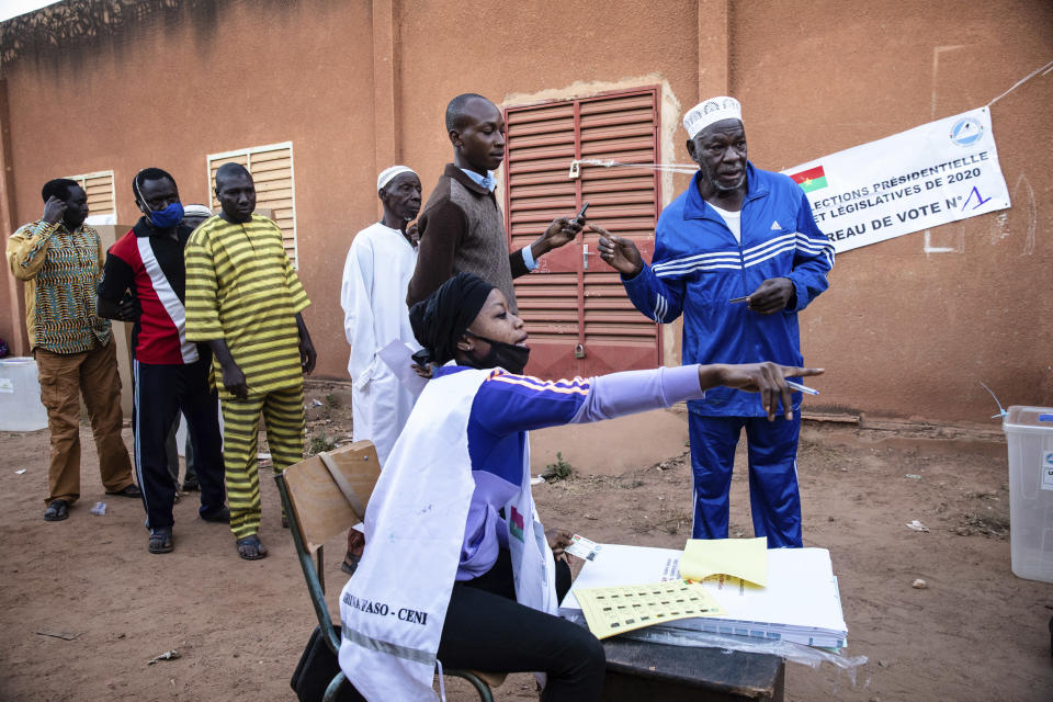People line up to vote in Burkina Faso's presidential and legislative elections as polling stations open in Ouagadougou, Sunday, Nov. 22, 2020. (AP Photo/Sophie Garcia)