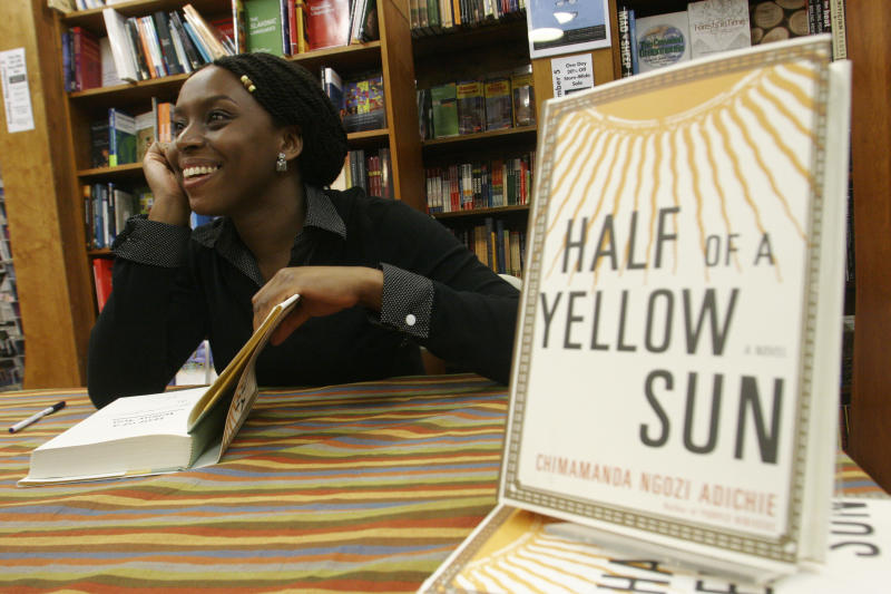 """FILE- In this Tuesday, Oct. 10, 2006, Nigerian author Chimamanda Ngozi Adichie autographs copies of her novel, Half of a Yellow Sun, after a reading at Harvard Bookstore in Cambridge, Mass. Nigerian censors are effectively banning the film """"Half of a Yellow Sun"""" and will not even say why, the Nigerian-British producers told The Associated Press Thursday amid suspicions that censors fear it could rouse tribal rivalries. The National Film and Video Censor Board insisted it has not banned the movie but delayed its registration over """"some unresolved issues which have to be sorted out."""" The movie's Nigeria premiere was set for last Friday. Invitations had been sent out and the film was to play in every cinema in the country. On Thursday, the board told the distributors that the film had not yet passed the registration process. """"No the film hasn't been banned but we can't show it, which technically is a ban,"""" Biyi Bandele said in a telephone interview from his home in London, where the movie placed among the 10 most popular at cinemas over the Easter weekend. It stars Oscar nominee Chiwetel Ejiofor and Thandie Newton and is an adaptation of the book by prize-winning novelist Chimamanda Ngozi Adichie. (AP Photo/JB Reed, file)"""