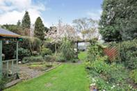 """<p>The garden is rather satisfying here, thanks to hedged borders, veg patches, <a href=""""https://www.housebeautiful.com/uk/garden/plants/a35429353/how-to-dry-flowers/"""" rel=""""nofollow noopener"""" target=""""_blank"""" data-ylk=""""slk:flower"""" class=""""link rapid-noclick-resp"""">flower</a> beds, a pond, and pristine lawns. It's the perfect spot for hunkering down after a long day. </p>"""