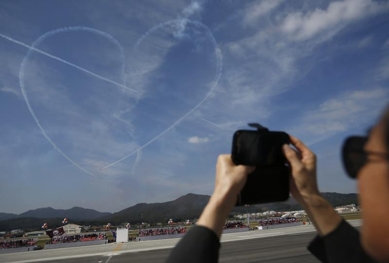 Man takes photographs of heart-shaped contrail left in sky by Black Eagles South Korean Air Force aerobatic team during celebrations to mark 65th anniversary of Korea Armed Forces Day, in Seongnam