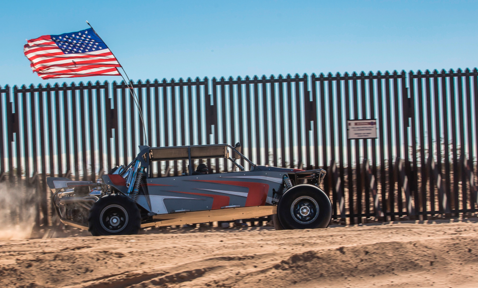 An off-road vehicle with a US flag drives near the US-Mexico border fence at the Imperial Sand Dunes Recreation Area east of Calexico, California, on December 30, 2018. (Photo: Apu Gomes / AFP) (Photo credit should read APU GOMES/AFP/Getty Images)