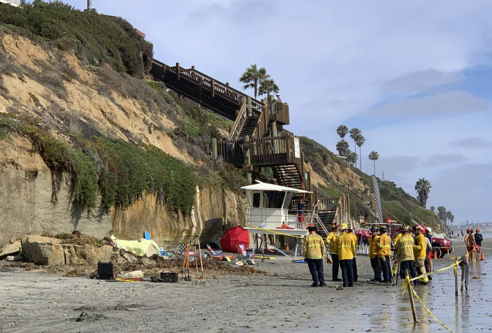 Lifeguards and search and rescue personnel work at the site of a cliff collapse at a popular beach Friday, Aug. 2, 2019, in Encinitas, Calif. At least one person was reportedly killed, and multiple people were injured, when an oceanfront bluff collapsed Friday at Grandview Beach in the Leucadia area of Encinitas, authorities said. (Hayne Palmour/The San Diego Union-Tribune via AP)