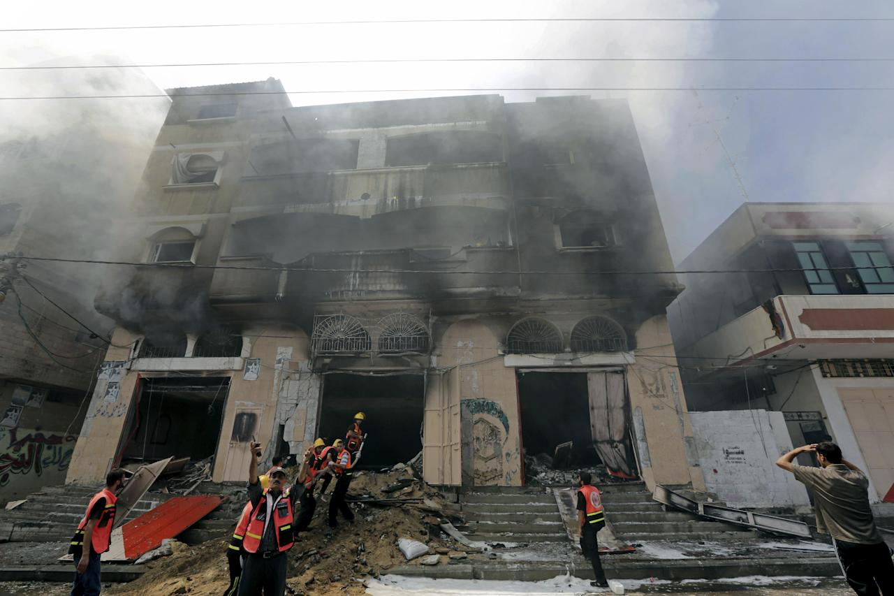 Palestinian firefighters try to extinguish a fire in a carpentry shop following an Israeli strike on a building in Gaza, northern Gaza Strip, Saturday, Aug. 23, 2014. (AP Photo/Adel Hana)