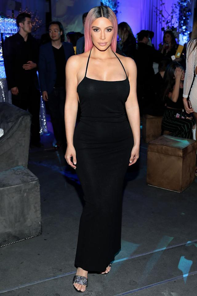 <p>in a strappy figure-hugging black maxi dress and glittery snakeskin heeled sandals while at a music release party in Hollywood.</p>