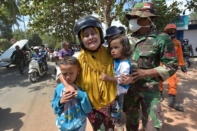 <p>An Indonesian woman cries next to her childern shortly after an aftershock hits the area in Tanjung on Lombok island on Aug. 9, 2018. (Photo: Adek Berry/AFP/Getty Images) </p>