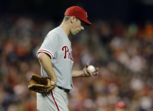 Philadelphia Phillies starting pitcher Cliff Lee looks at the ball during the sixth inning of a baseball game against the Washington Nationals at Nationals Park, Saturday, Aug. 10, 2013, in Washington. (AP Photo/Alex Brandon)