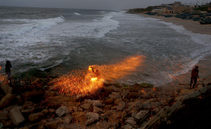 A man swings fireworks during the Muslim holy fasting month of Ramadan, on the beach of Gaza City, Monday, April 26, 2021. (AP Photo/Hatem Moussa)