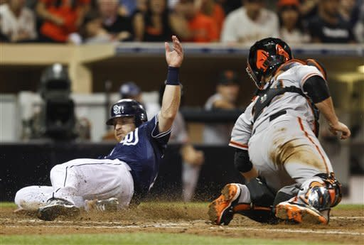 San Diego Padres' Logan Forsythe beats the attempted tag by San Francisco Giants catcher Buster Posey while scoring on a hit by Yasmani Grandal during the fifth inning of a baseball game Saturday, Sept. 29, 2012, in San Diego. (AP Photo/Lenny Ignelzi)