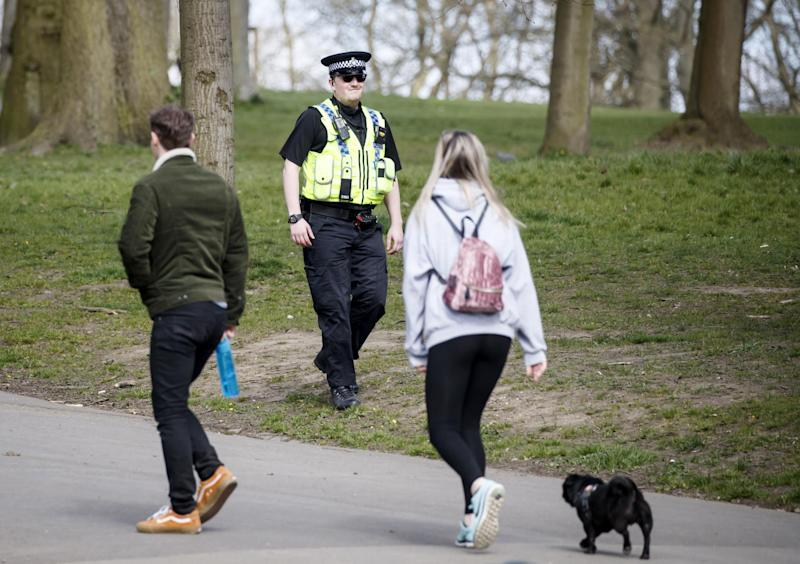 A policeman walks past a people exercising with a dog in Roundhay Park, Leeds: PA