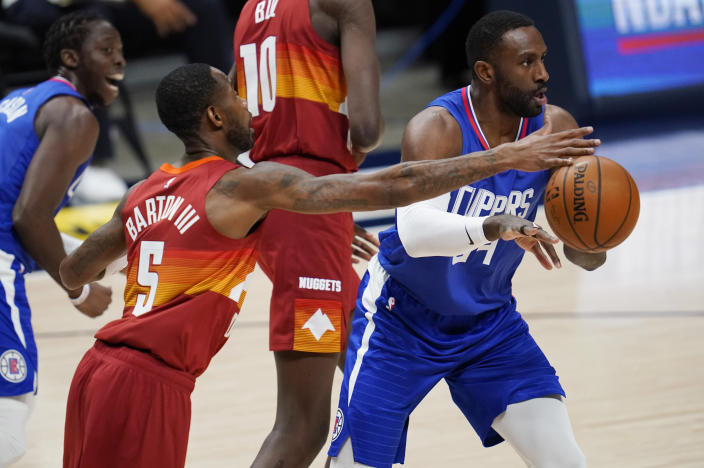 Denver Nuggets forward Will Barton, left, tries to block a pass by Los Angeles Clippers forward Patrick Patterson during the first half of an NBA basketball game Friday, Dec. 25, 2020, in Denver. (AP Photo/David Zalubowski)