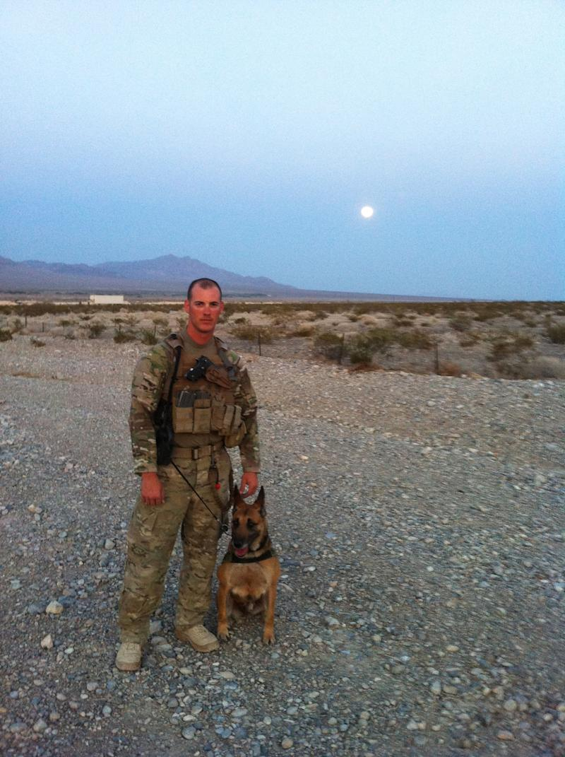 """This 2012 publicity photo provided by Animal Planet shows pre-deployment photos of Air Force Tech. Sgt. Leonard Anderson and a bomb-detecting dog, Azza, an 8-year-old Belgian Malinois at training in Las Vegas. After the Nevada training, Air Force Tech. Sgt. Anderson and Azza were sent to Kandahar Province, in Afghanistan. Animal Planet television special """"Glory Hounds,"""" included coverage of Air Force Tech. Sgt. Anderson, a military dog handler and his team, when they embedded four camera crews with front line troops for six weeks. (AP Photo/Animal Planet)"""