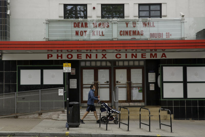 The independent Phoenix Cinema with a coronavirus message written where the name of a movie would normally appear, stands temporarily closed as part of the nationwide coronavirus lockdown in East Finchley, north London, Friday, May 22, 2020. (AP Photo/Matt Dunham)