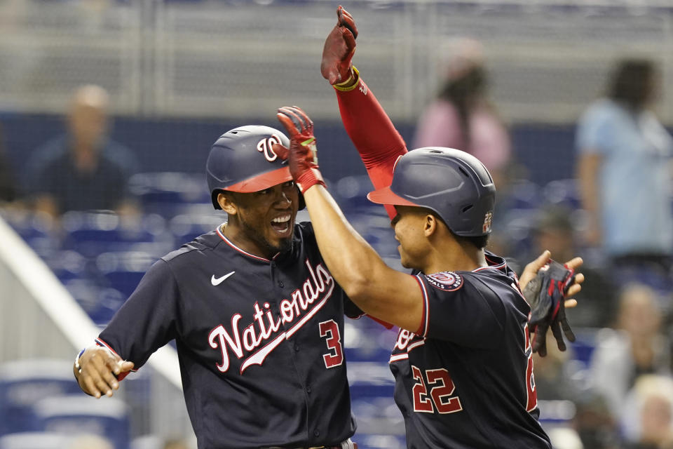 Washington Nationals' Alcides Escobar (3) cheers Juan Soto (22) after Soto hit a two-run home run during the third inning of a baseball game against the Miami Marlins, Wednesday, Sept. 22, 2021, in Miami. (AP Photo/Marta Lavandier)