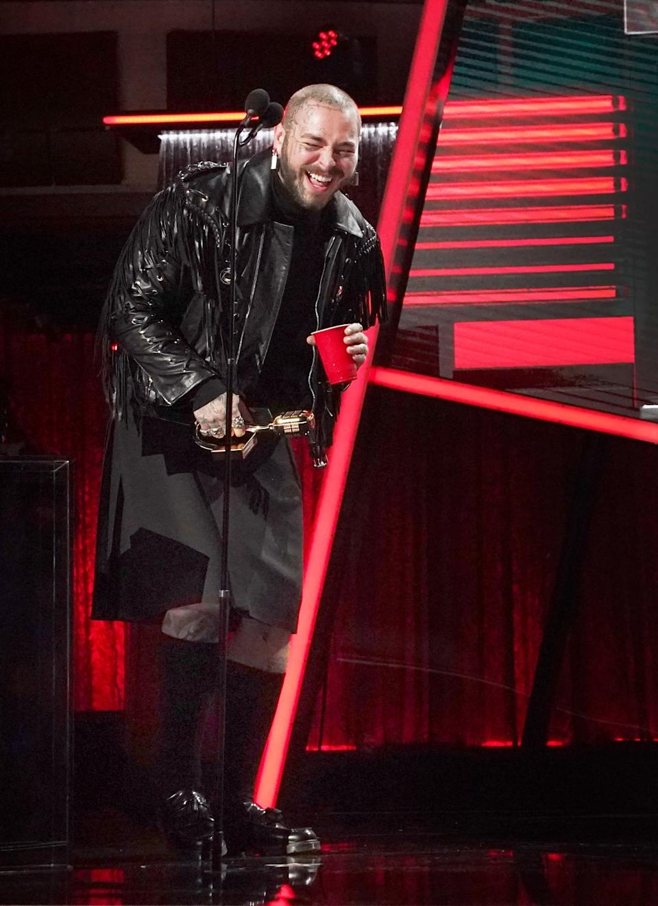 Post Malone laughs as he accepts an award.