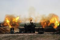 Israeli soldiers work in an artillery unit as it fires near the border between Israel and the Gaza strip, on the Israeli side