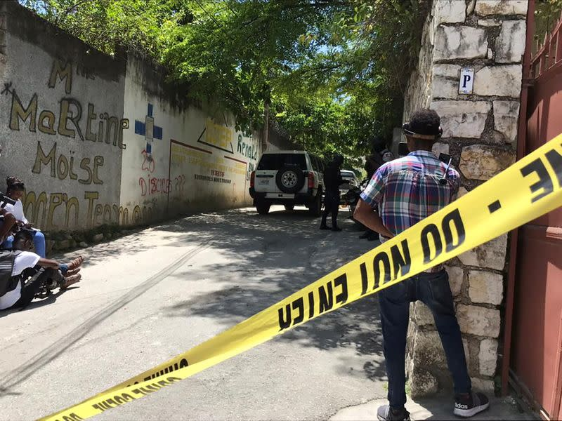 Journalists stand next to a yellow police cordon near the residence of Haiti's President Jovenel Moise after he was shot dead by unidentified attackers, in Port-au-Prince