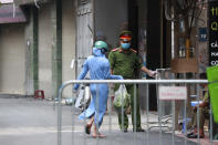 A woman leaves the food shopping for her relatives at the barricaded entrance to the residence of a confirmed COVID-19 case in Hanoi, Vietnam on Wednesday, July 29, 2020. Vietnam intensifies protective measures as the number of locally transmissions, starting at a hospital in the popular beach city of Da Nang, keeps increasing since the weekend. (AP Photo/Hau Dinh)