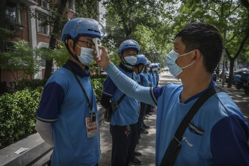 BEIJING, CHINA - JULY 01: A Chinese courier driver has his temperature checked for COVID-19 prevention before starting his shift on July 1, 2020 in Beijing, China. While Chinese government medical officials have said they believe they have contianed the outbreak, authorities are trying to control the spread of COVID-19 infections linked to the Xinfadi wholesale food market, Beijing's biggest supplier of produce and meat. More than 8 million people have undergone nucleic acid tests for COVID-19 at dozens of sites across the city in recent days, with officials using contact tracing to target high and middle risk areas and people who may have had contact with the market or food that came from there. Several neighborhoods have been locked down and a number of other food markets have been closed. (Photo by Kevin Frayer/Getty Images)