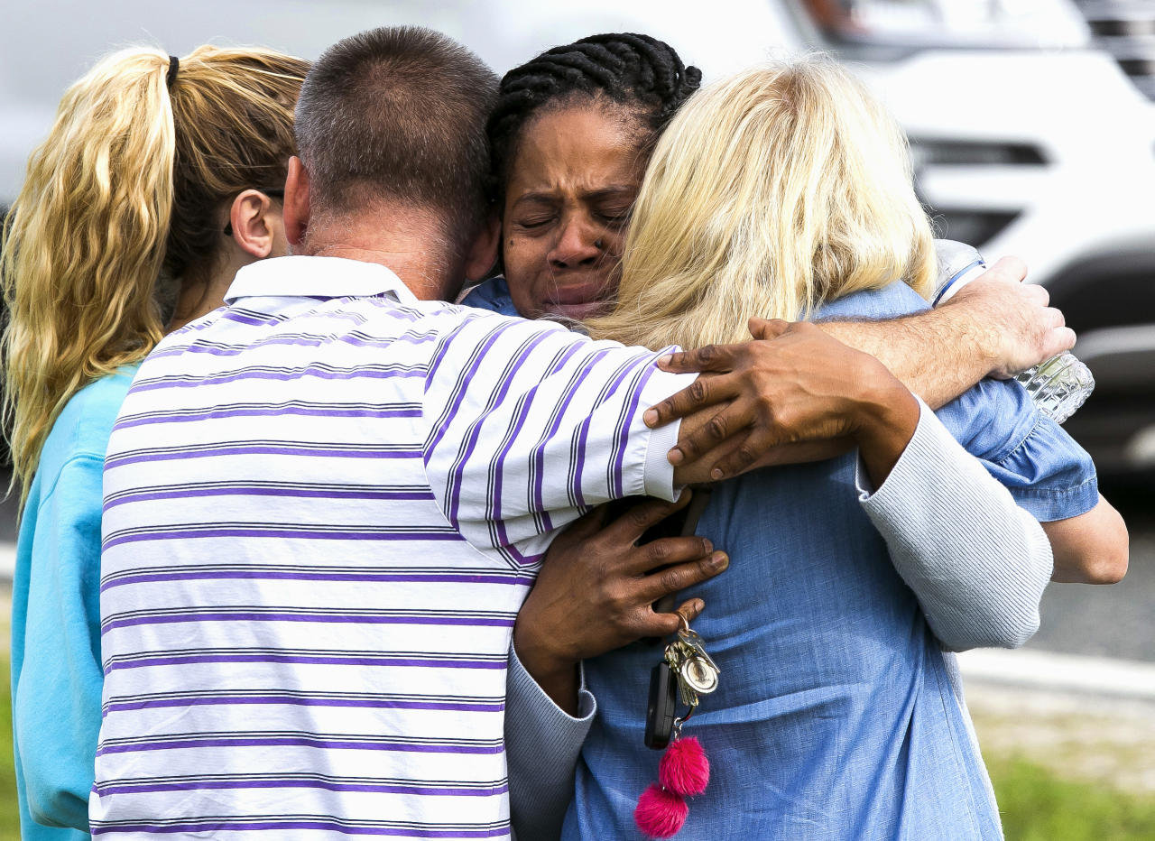 <p>Nikki Brown, center, hugs others in front of Forest High School Friday, April 20, 2018 in Ocala, Fla. (Photo: Doug Engle/Star-Banner via AP) </p>