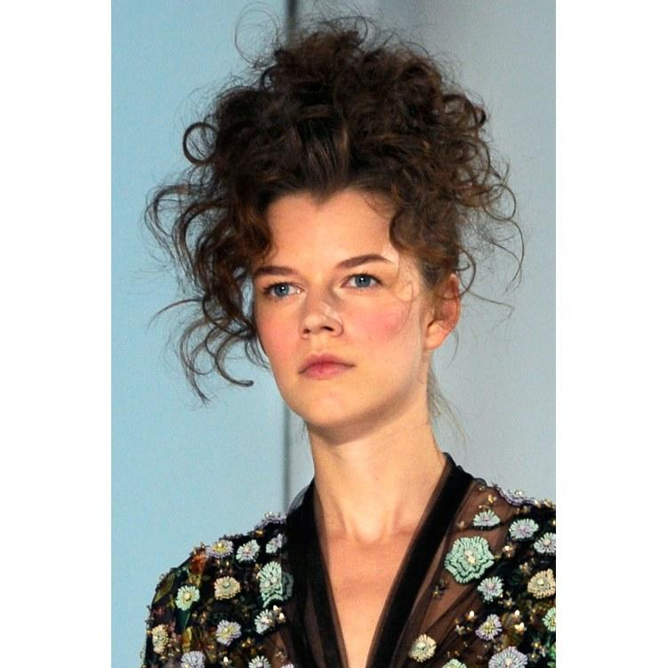 <p>It's safe to assume that hairstylist Thom Priano isn't afraid of heights. At the Reem Acra show, soft spirals were piled sky high on top of an otherwise simple French twist. The cascade of curls gave the updo an added touch of whimsy and romance.</p>