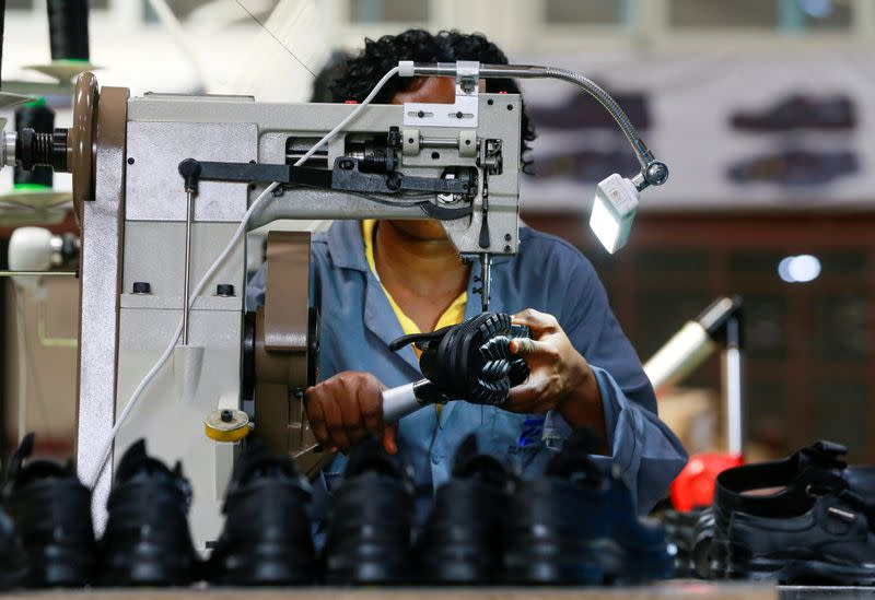 An employee works on a shoe inside a Bata shoe factory in Abuja