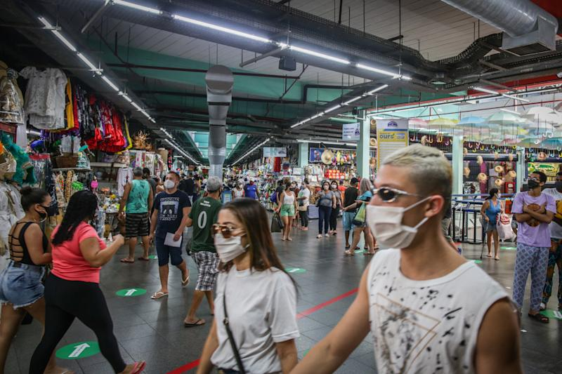 RIO DE JANEIRO, BRAZIL - JUNE 17: Shoppers wearing face masks walk in a crowded Mercadao de Madureira, at the Madureira neighborhood amidst the coronavirus (COVID-19) pandemic on June 17, 2020 in Rio de Janeiro, Brazil. Mercadao de Madureira is one of the most popular trading centers in Rio de Janeiro. The city of Rio de Janeiro started today the second phase of the quarantine flexibilization. The decree determines the return of 100% of the bus fleet and some commercial establishments following distance rules such as reduced opening hours, restricting the flow of people and maintaining hygiene standards. (Photo by Andre Coelho/Getty Images)