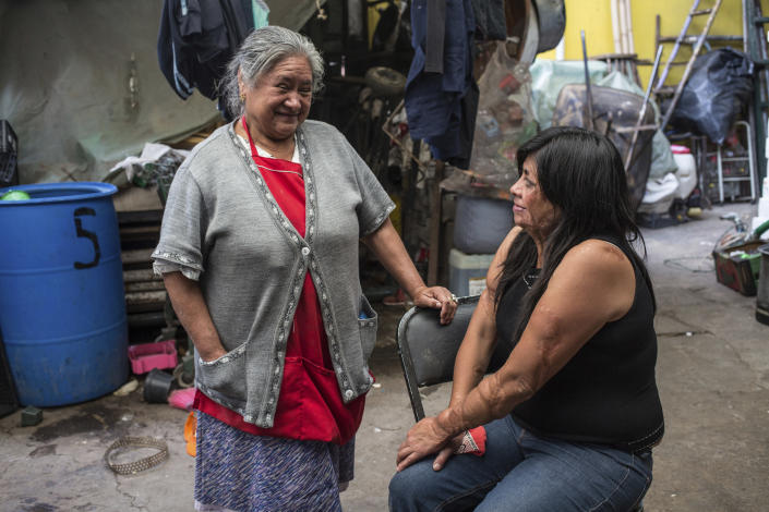 Elisa Xolalpa, who survived an acid attack while tied to a post by her ex-partner 20 years ago when she was 18, talks with her mother Carmen Martinez in the patio of her parent's home in Mexico City, Saturday, June 12, 2021. Mexico City's special prosecutor for feminicides, Sayuri Herrera, said that more acid attacks are being registered in Mexico, and that her office is reviewing older cases that were originally classified as serious injuries to see if they can be reclassified as attempted feminicide like Xolalpa's. (AP Photo/Ginnette Riquelme)