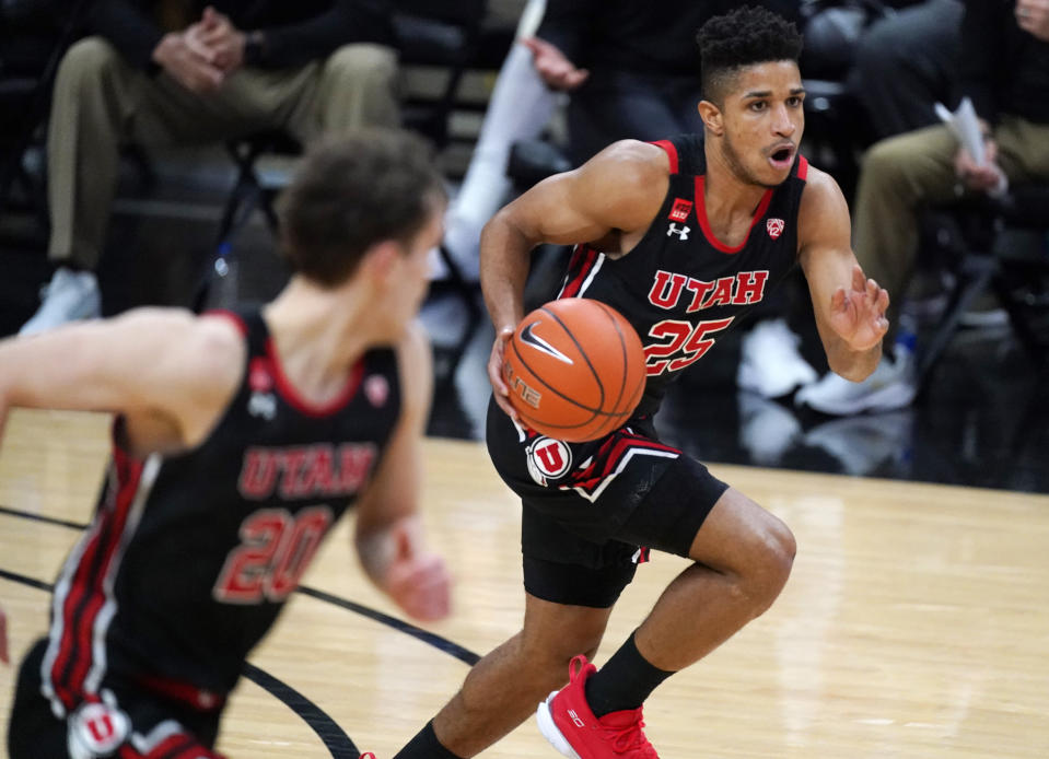 Utah guard Alfonso Plummer (25) brings the ball upcourt while flanked by forward Mikael Jantunen in the second half of an NCAA college basketball game against Colorado, Saturday, Jan. 30, 2021, in Boulder, Colo. (AP Photo/David Zalubowski)