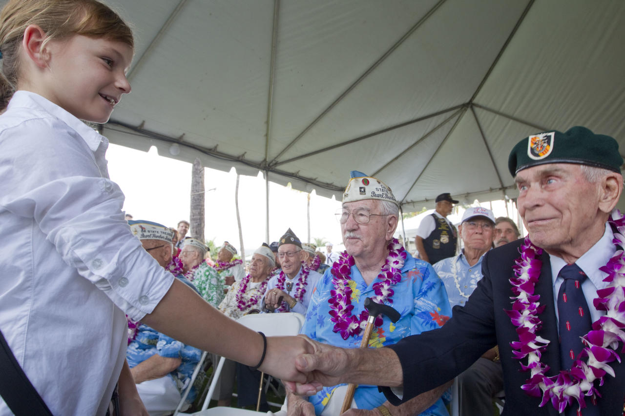 Gabi Shultz, 10, resident of Joint Base Pearl Harbor Hickam, meets Pearl Harbor survivor Sam Clower, center, of Sacramento, Calif. and Ab Brum, right, retired United States Army Special Forces, of Kaneohe, Hawaii, Friday, Dec. 7, 2012, at Pearl Harbor. Many of the Pearl Harbor Veterans gathered at the World War II Valor In The Pacific National Monument remembering the 71th anniversary of the Dec. 7, 194 Japanese surprise attack on Pearl Harbor in Honolulu. (AP Photo/Eugene Tanner)