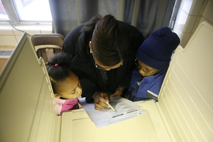 A mother votes in Chicago in 2008 as her kids look on. (Chuck Berman/Chicago Tribune/MCT via Getty Images)